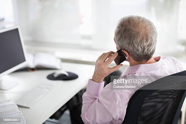 Businessman on cell phone at desk