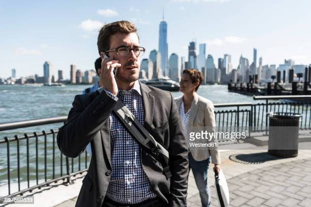 USA, businessman on cell phone at New Jersey waterfront with view to Manhattan