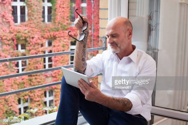 businessman on cell phone at the window - haarausfall stock-fotos und bilder
