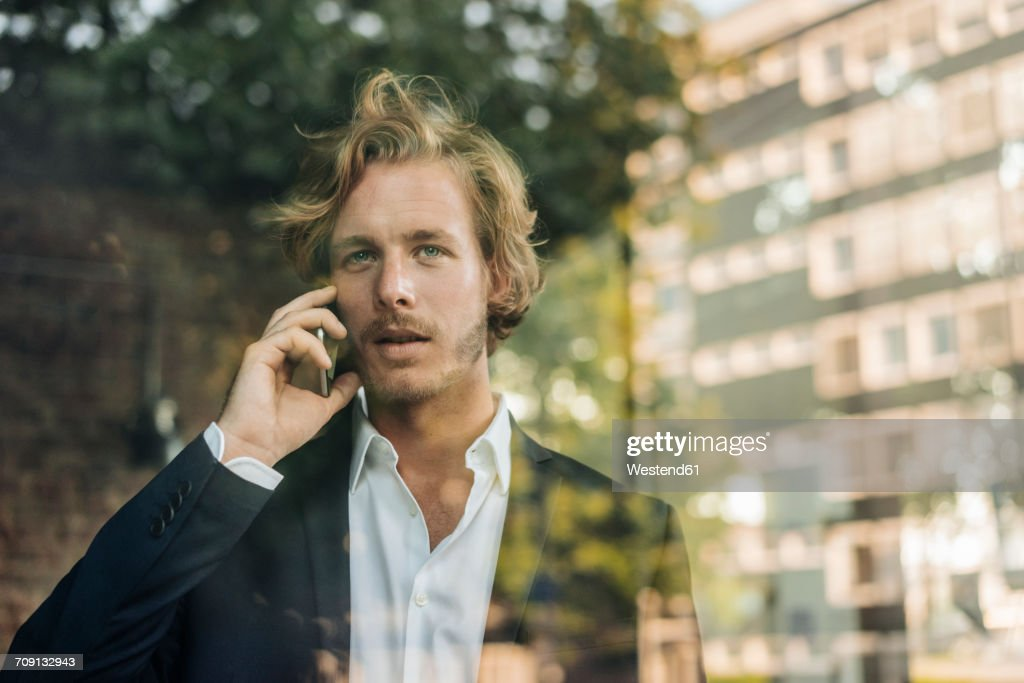 Businessman on cell phone behind windowpane : Stock-Foto