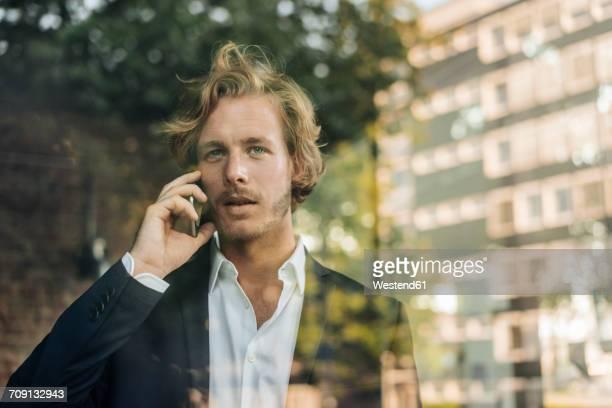 Businessman on cell phone behind windowpane
