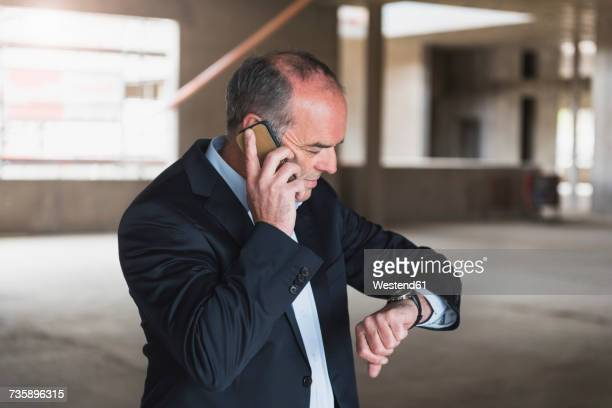 Businessman on cell phone in building under construction checking the time