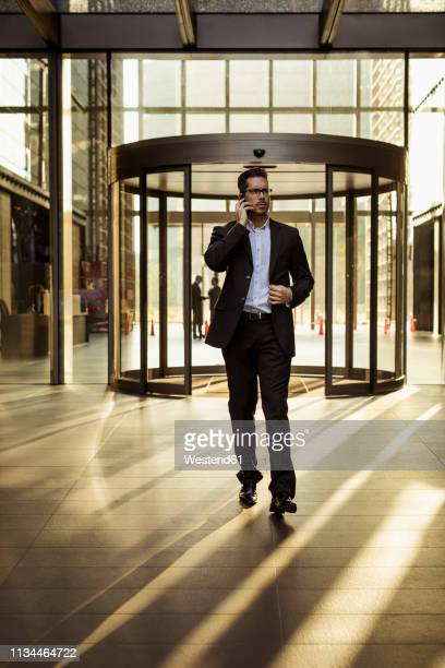 businessman on cell phone in foyer of an office building - incidental people stock pictures, royalty-free photos & images