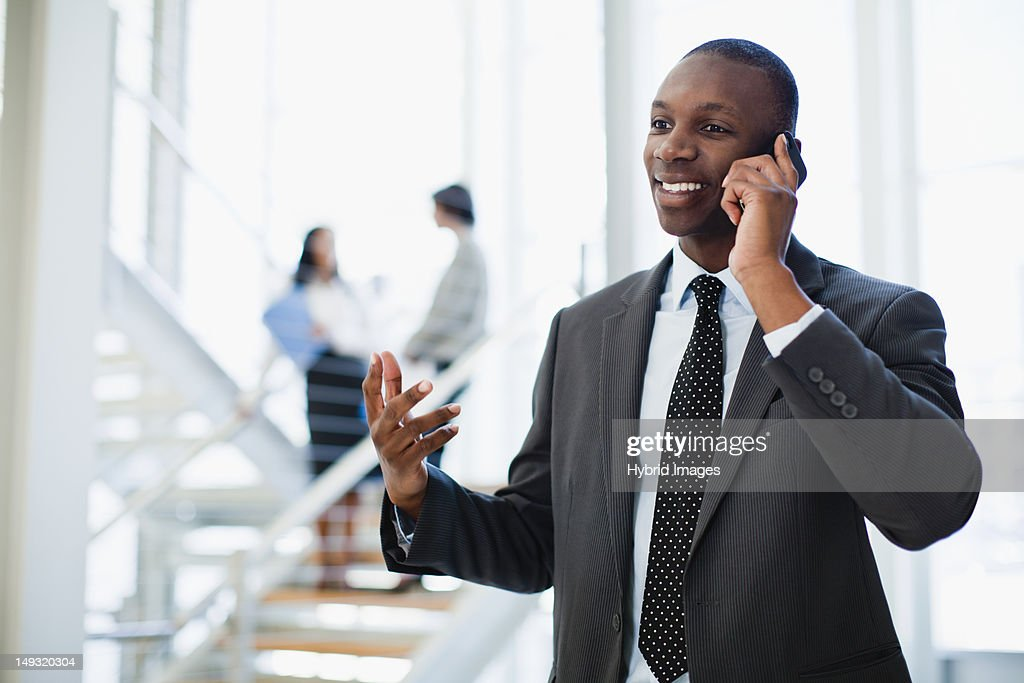 Businessman on cell phone in office : Stock Photo