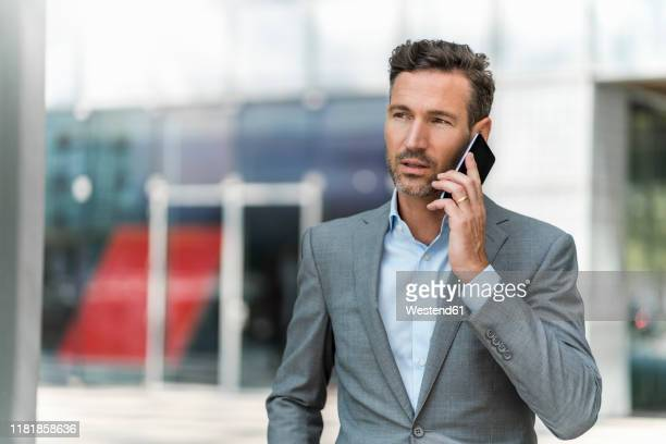 businessman on cell phone in the city - grey suit stock pictures, royalty-free photos & images