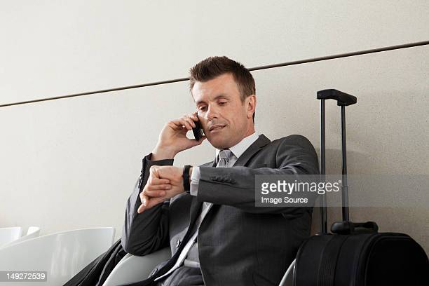 Businessman on cell phone waiting with luggage and checking watch