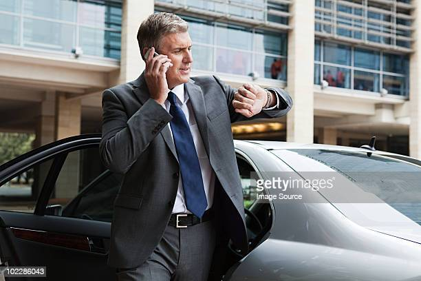 Businessman on cellphone looking at watch