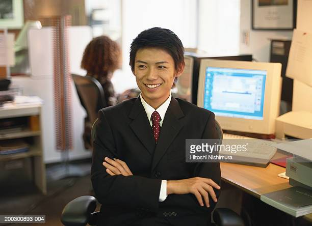 Businessman on chair with arms crossed, smiling