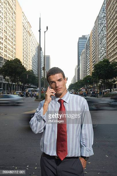 Businessman on city street using mobile phone