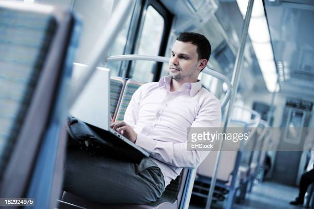 Businessman on Commuter Train with Laptop Computer