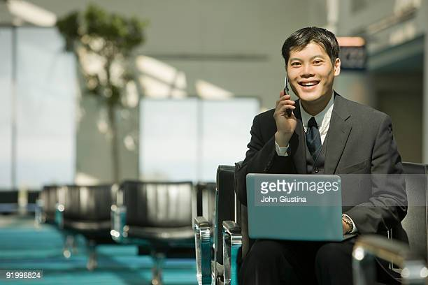 Businessman on computer and phone in airport.