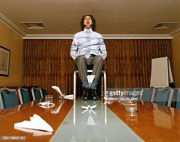 businessman on conference room table bound to chair, screaming - man tied to chair stock photos and pictures