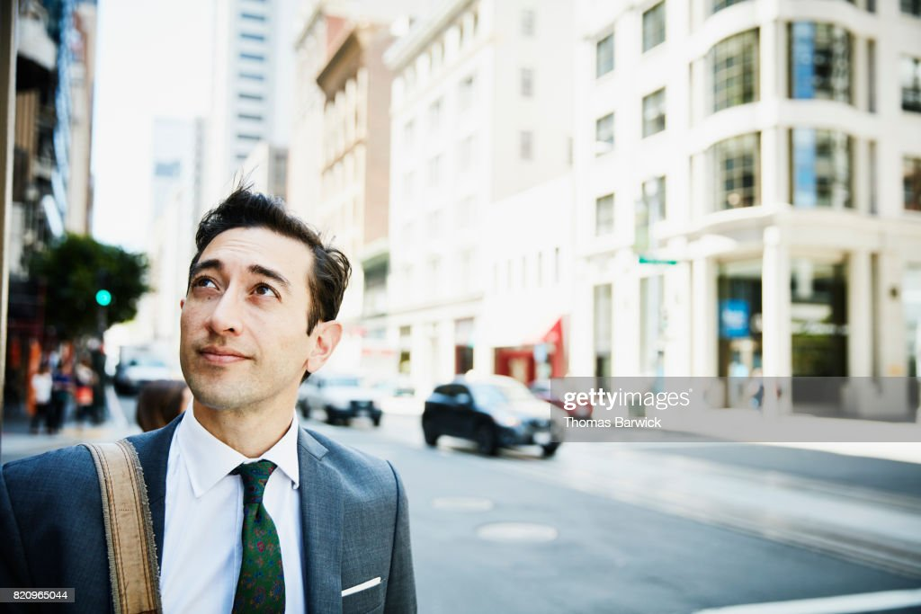 Businessman on downtown street looking at city skyline : Stock Photo