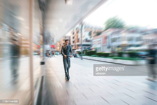 businessman on electric push scooter - electric scooter stock pictures, royalty-free photos & images