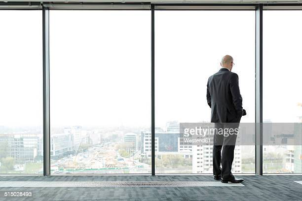 businessman on empty office floor looking out of window - aussicht genießen stock-fotos und bilder
