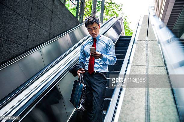 Businessman on escalator exiting from the subway