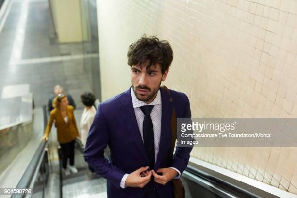 Businessman on escalator in train station