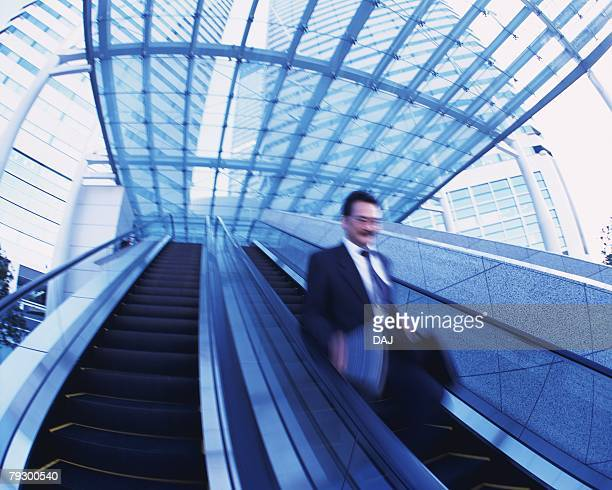 Businessman on Escalator, Low Angle View, Long Exposure