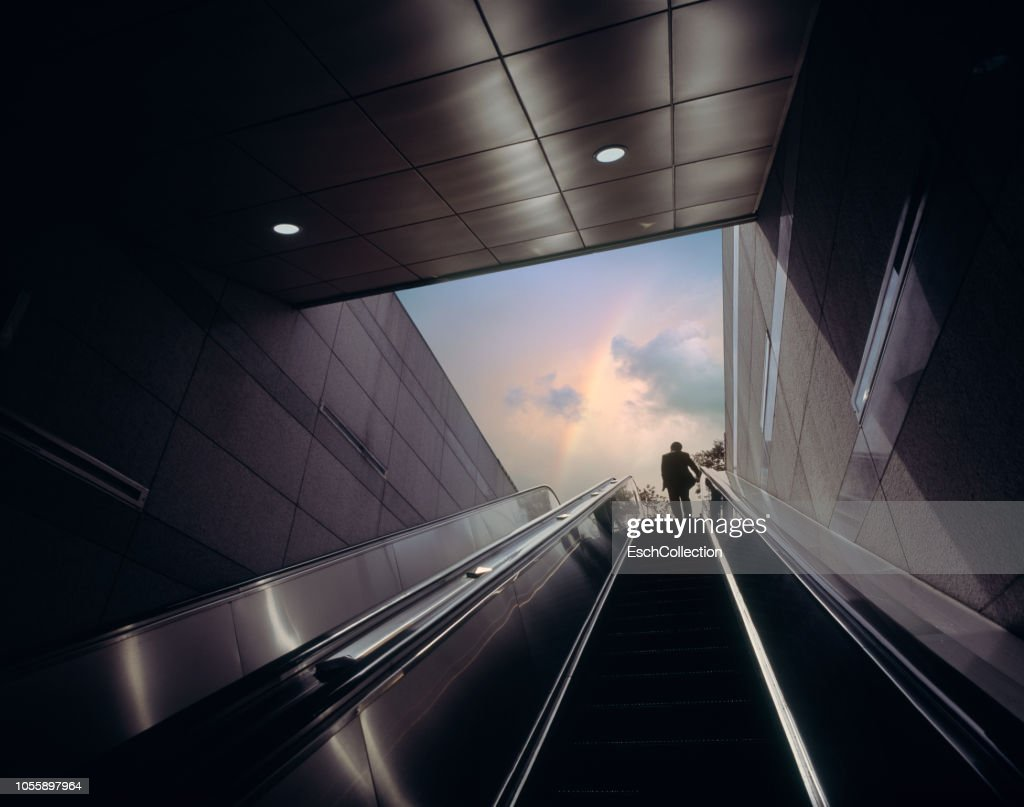 Businessman on escalator moving towards sky with rainbow : Stock Photo