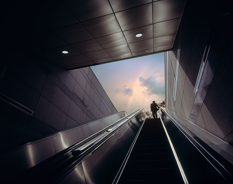 Businessman on escalator moving towards sky with rainbow - gettyimageskorea
