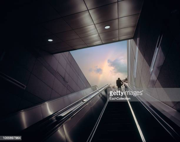 Businessman on escalator moving towards sky with rainbow