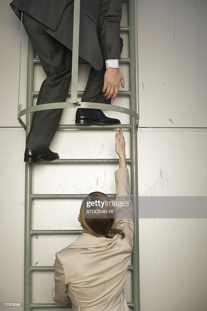 Businessman on fire escape, reaching down to businesswoman's hand below : Photo