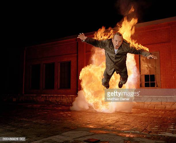 Businessman on fire in mid air, night