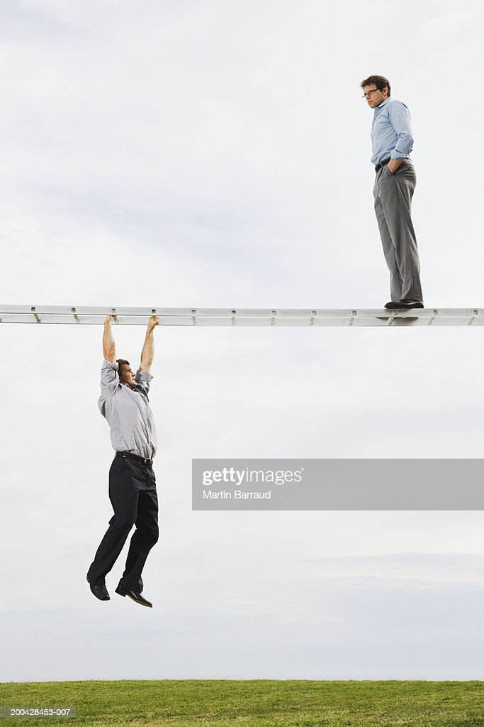 Businessman on horizontal ladder watching businessman suspended below : Stock Photo