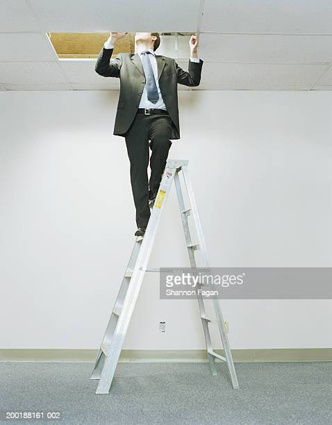 Businessman on ladder looking above ceiling panel