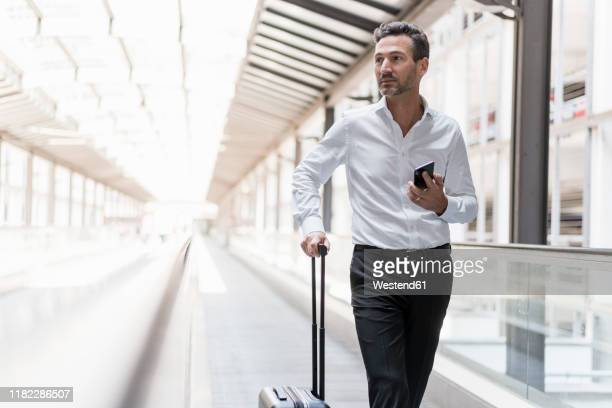 businessman on moving walkway at the airport - abbigliamento elegante foto e immagini stock