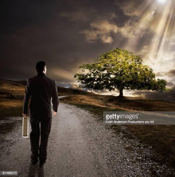 Businessman on path towards sun ray