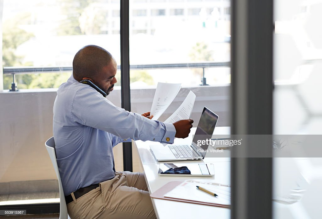 Businessman on phone and looking threw papers : Stock Photo