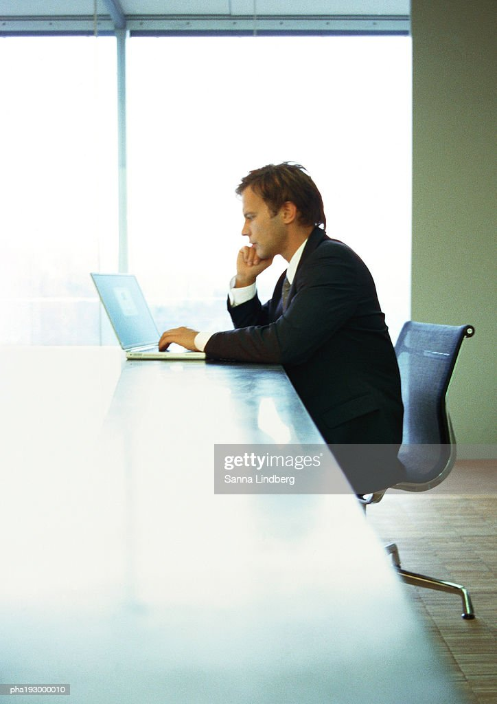 Businessman on phone and working on computer. : Stockfoto