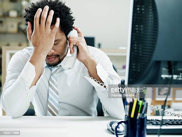 businessman on phone at desk hand on forehead - reizen stock-fotos und bilder