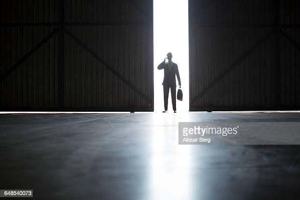 Businessman on phone in warehouse doorway