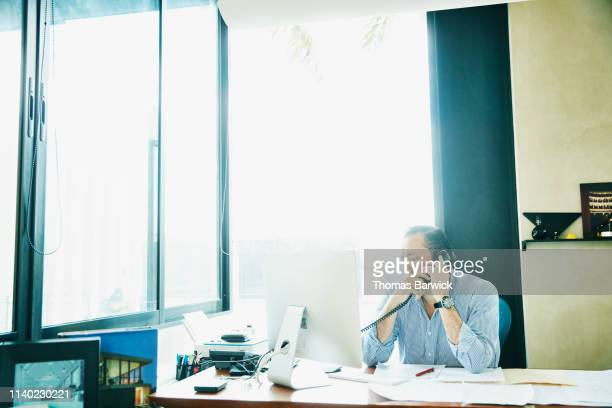 Businessman on phone while working on computer in office