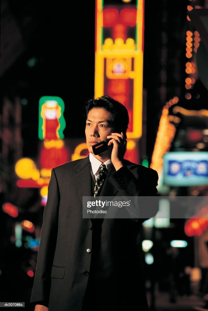 Businessman on phone with neon behind : Stock Photo