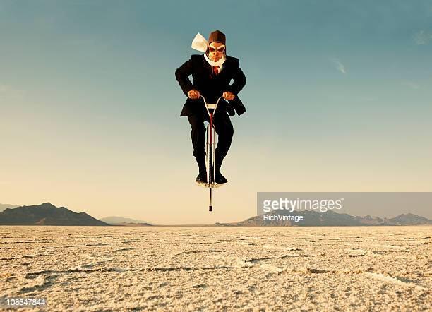 Businessman on Pogo Stick in Desert