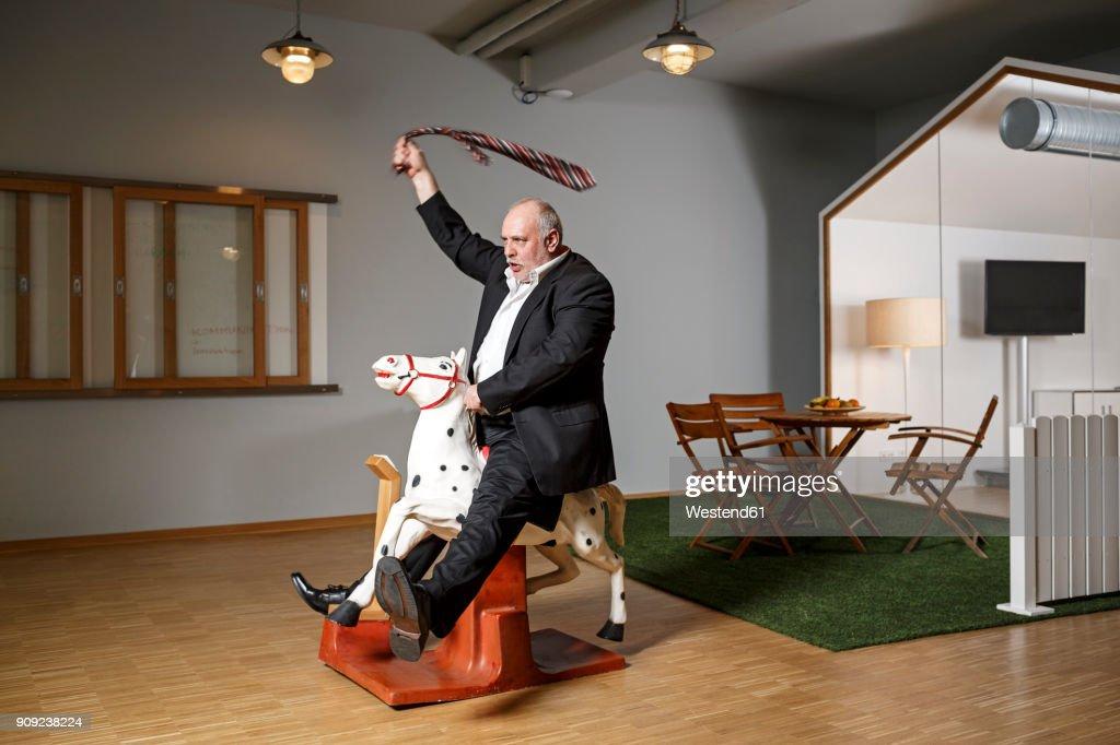 Businessman on rocking horse pretending to ride : Stock Photo