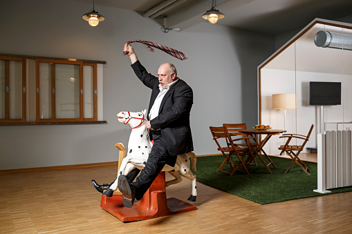 Businessman on rocking horse pretending to ride - gettyimageskorea