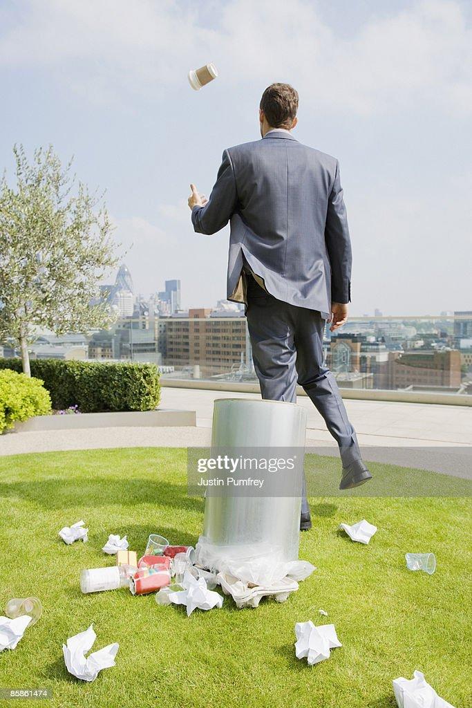 Businessman on rooftop by dustbin, rear view : Stock-Foto