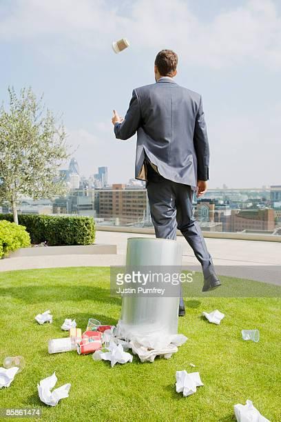 Businessman on rooftop by dustbin, rear view