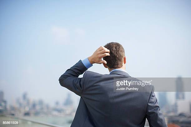 Businessman on rooftop, close up, rear view