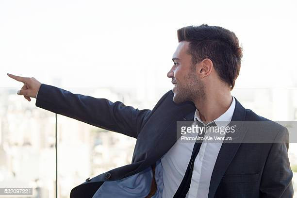 Businessman on rooftop, pointing at view