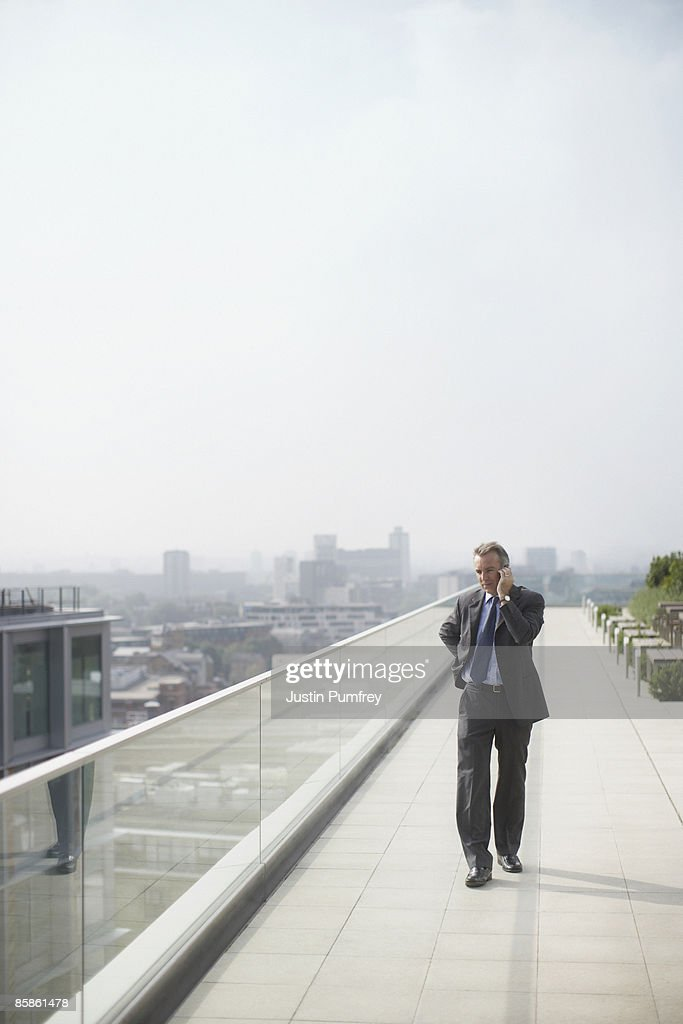 Businessman on rooftop using mobile : Stock-Foto