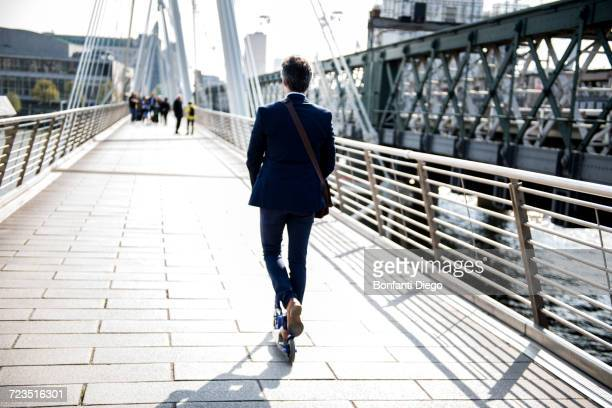 Businessman on scooter, Hungerford Bridge, London, UK