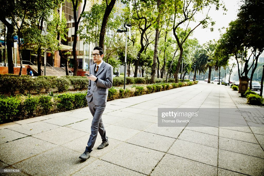 Businessman on sidewalk looking at smartphone : Stock Photo
