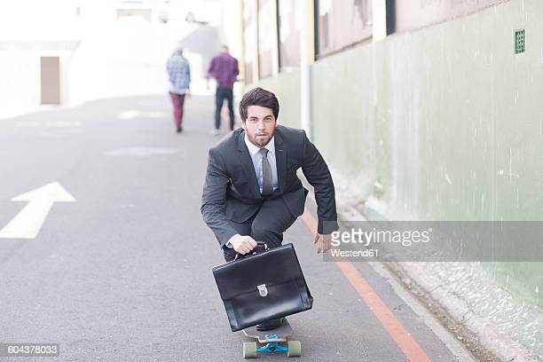 Businessman on skateboard riding down the street