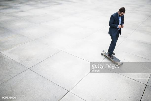 Businessman on skateboard using his phone