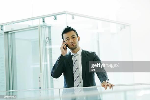 Businessman on smart phone in elevator hall